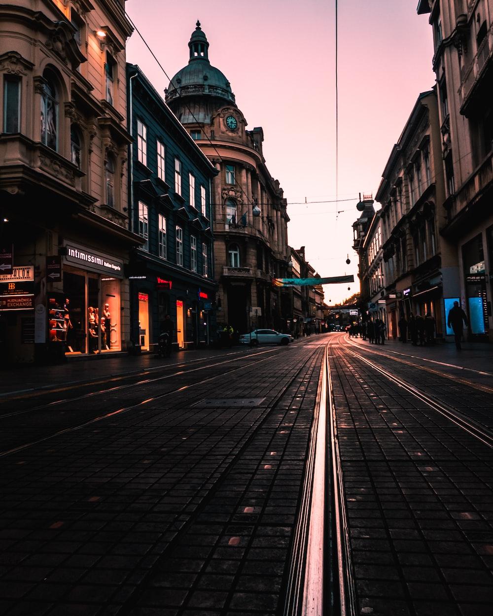 black concrete road between buildings at golden hour