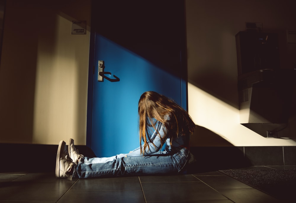 girl sits on the floor in front of the blue painted door