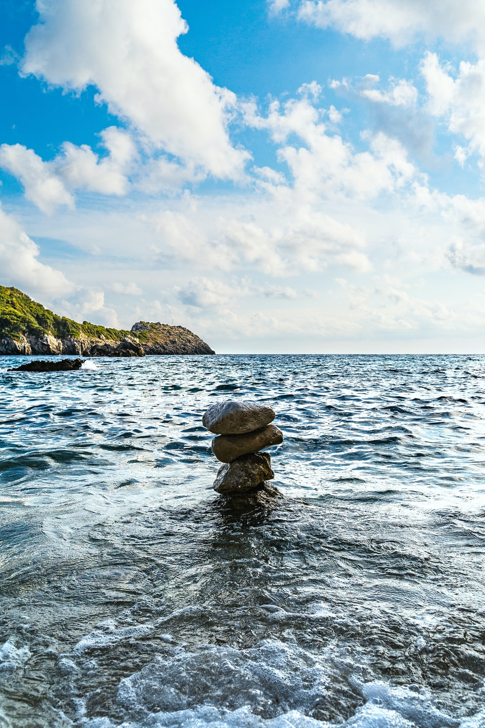 stock of stones on body of water during daytime
