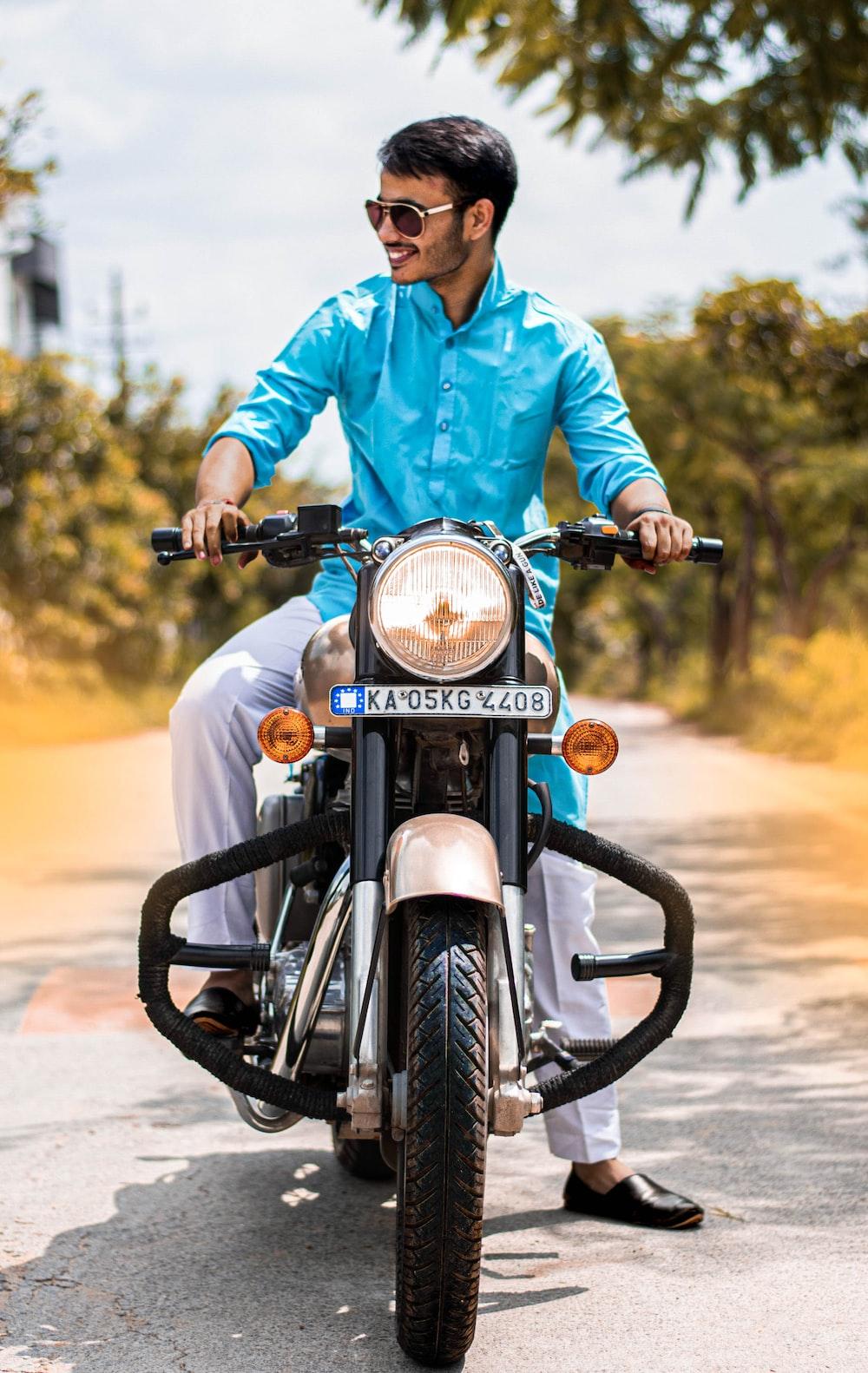man in blue dress shirt riding motorcycle