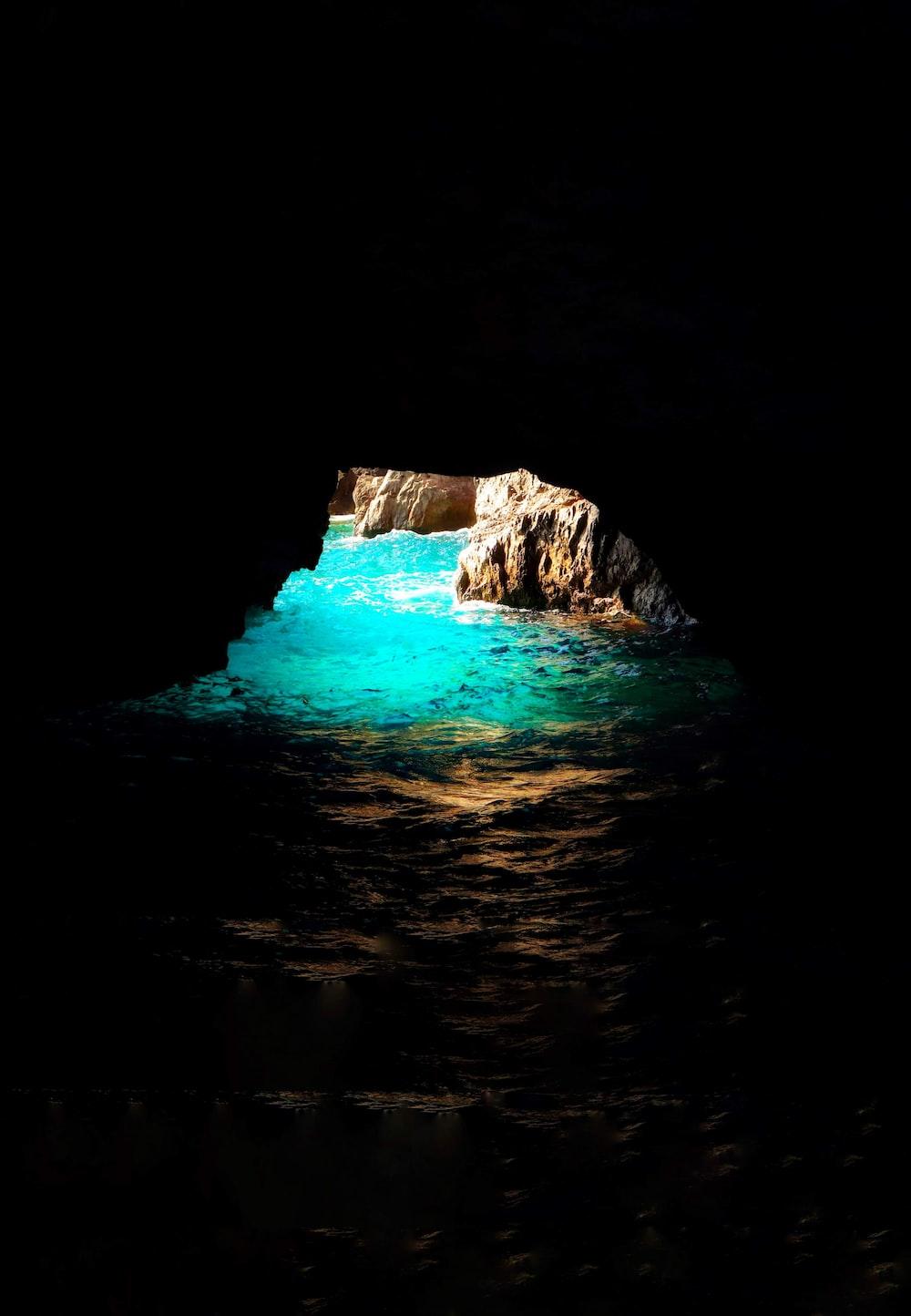 wavy ocean under cave