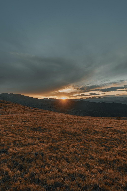 brown grass land across mountain during sunset