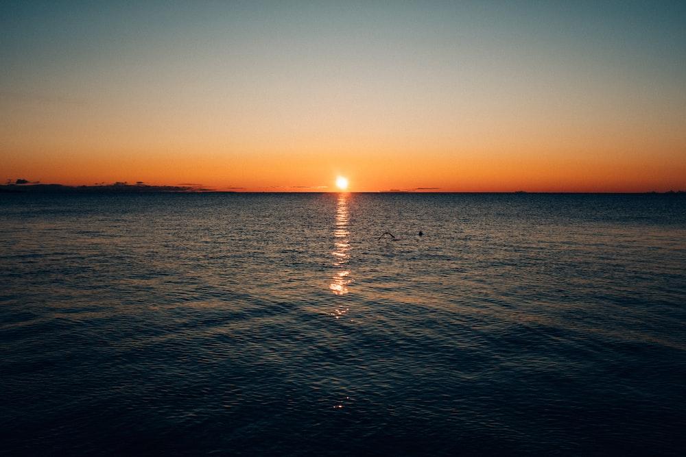 body of water under brown sky at golden hour