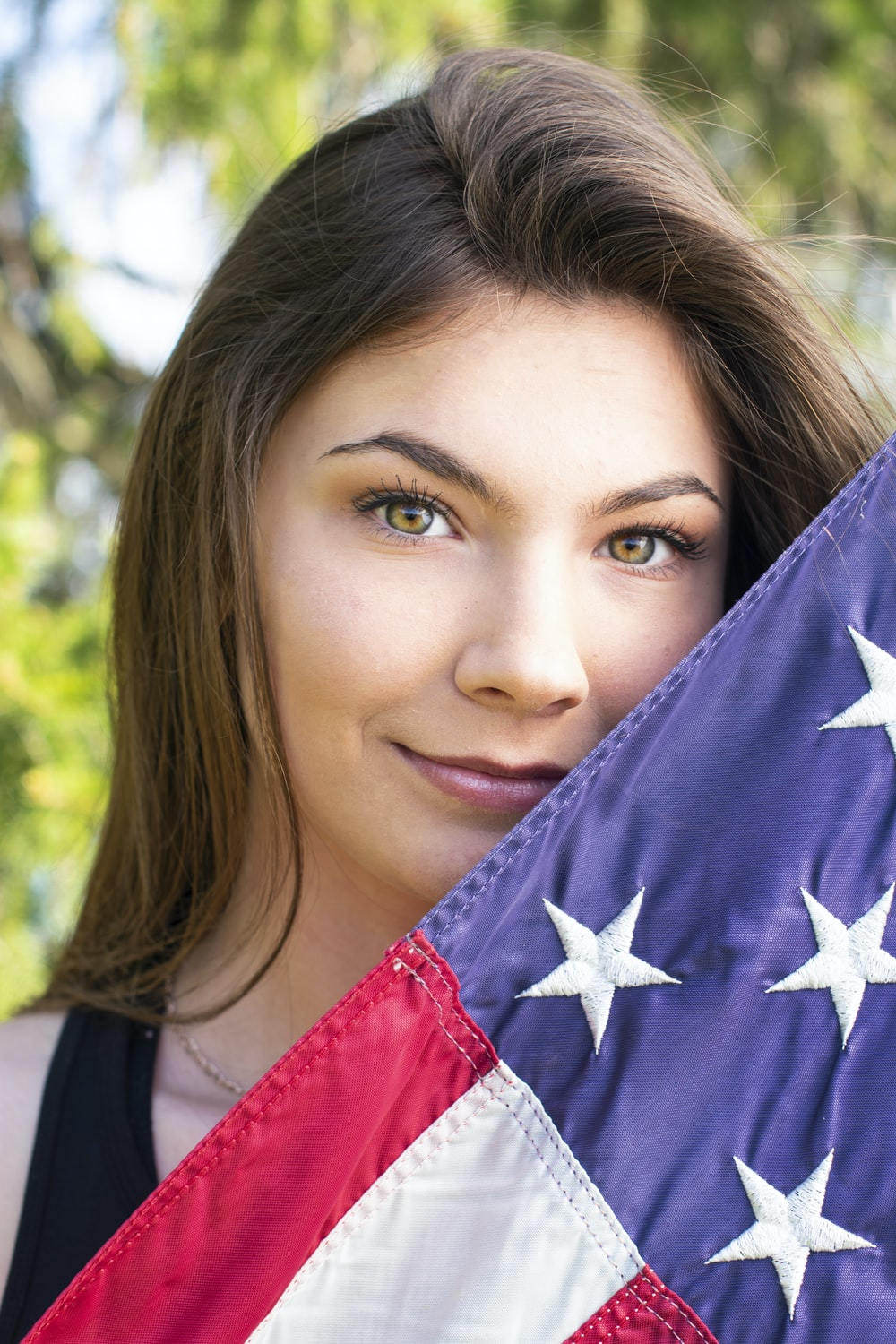 woman holding blue, white, and pink flag