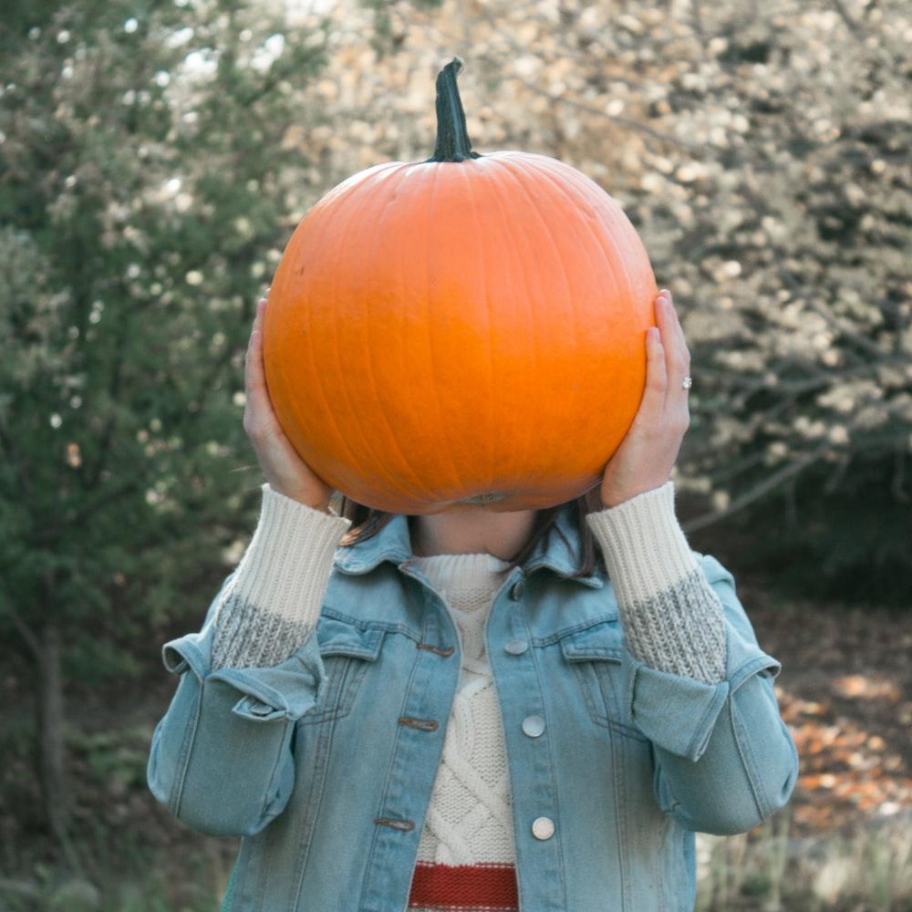 person holding orange pumpkin outdoors