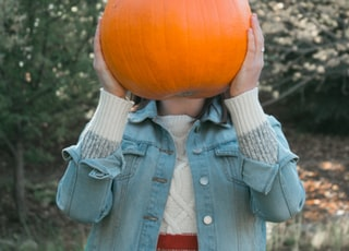 person holding orange pumpkin outdoors
