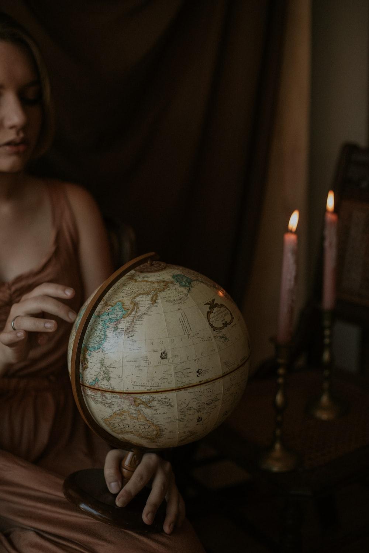 woman wearing brown dress holding white globe