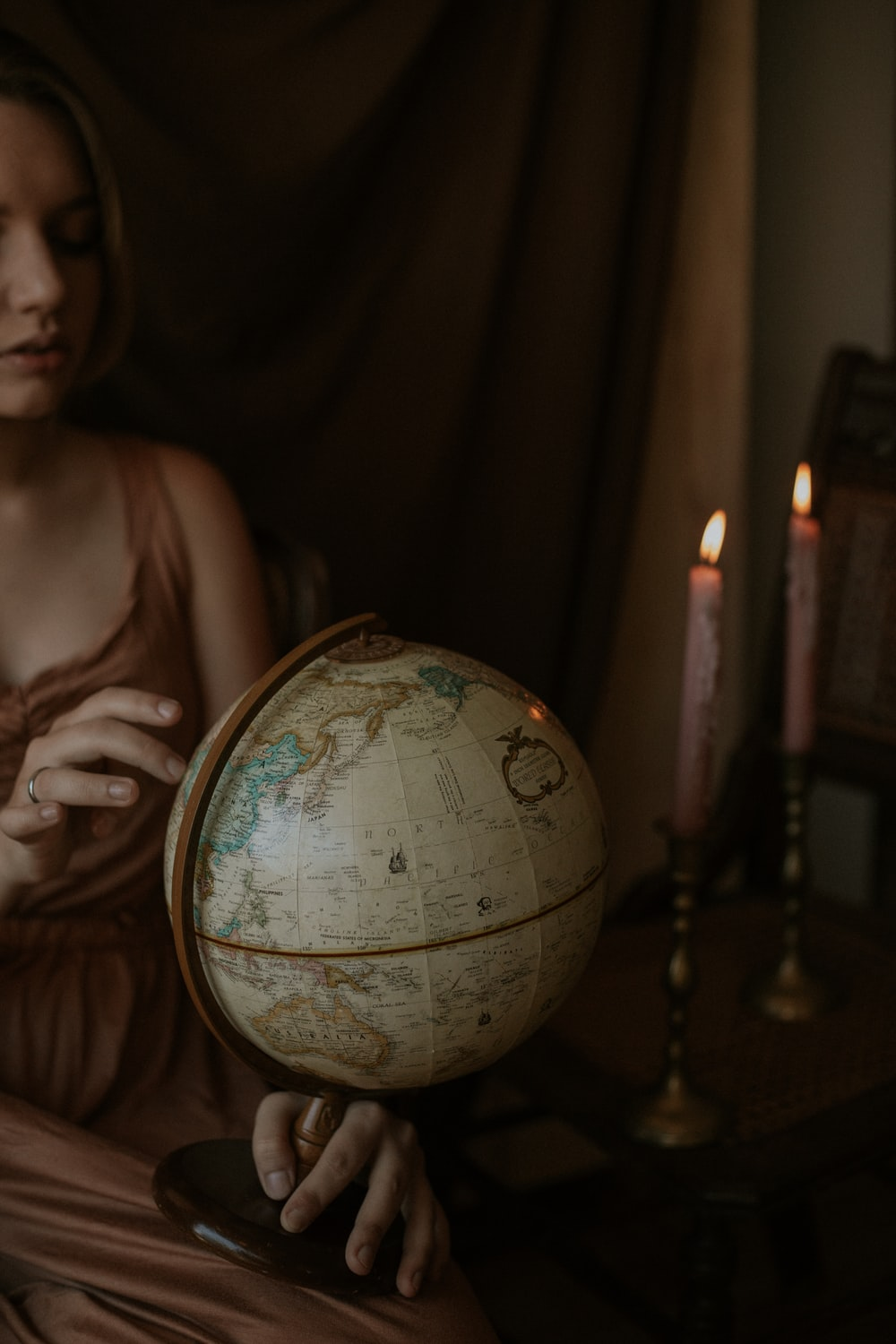 woman wearing brown dress holding white globe