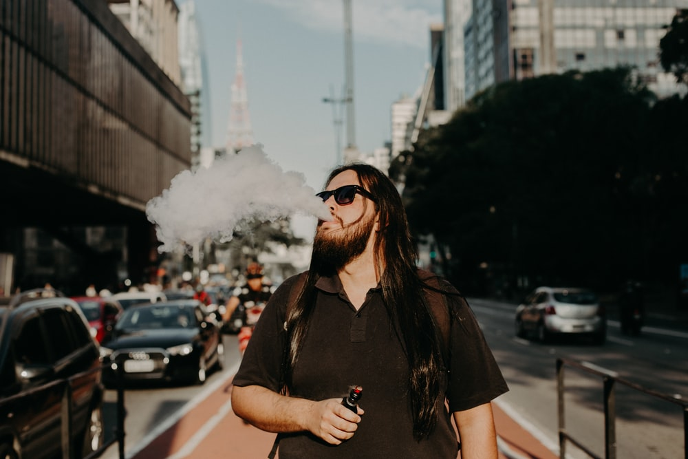 man in sunglasses vaping during daytime