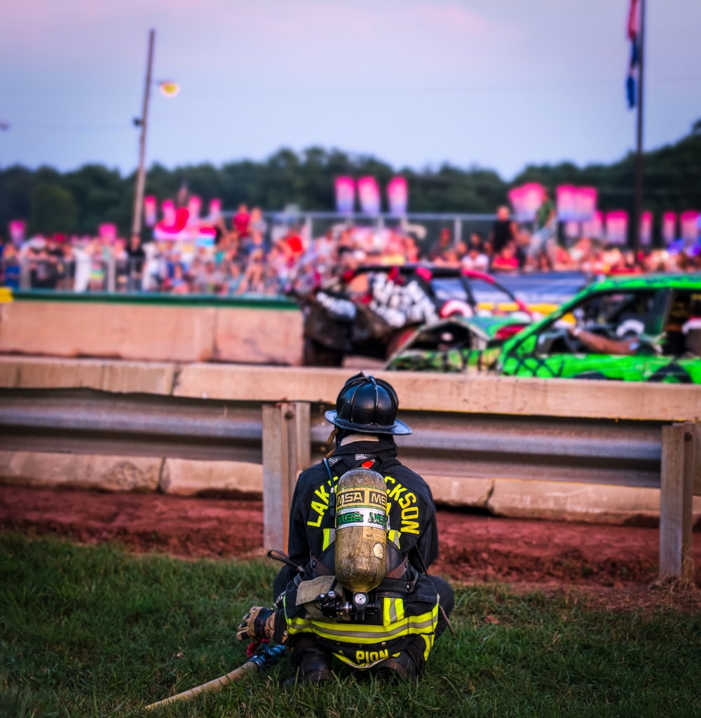 firefighter sitting on grass near stock cars on road