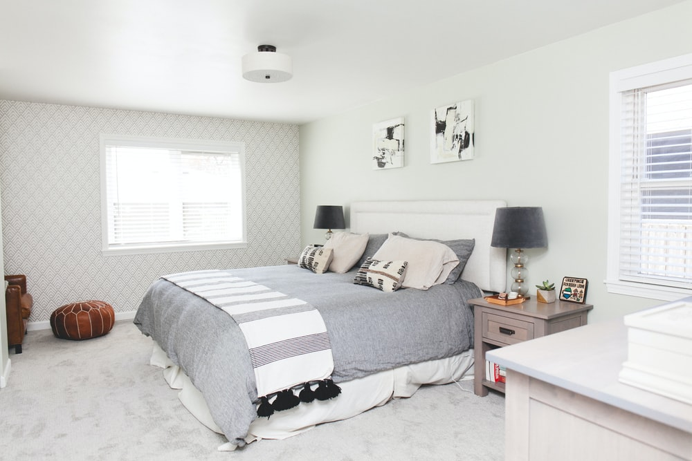 bed with comforter beside nightstand with table lamp