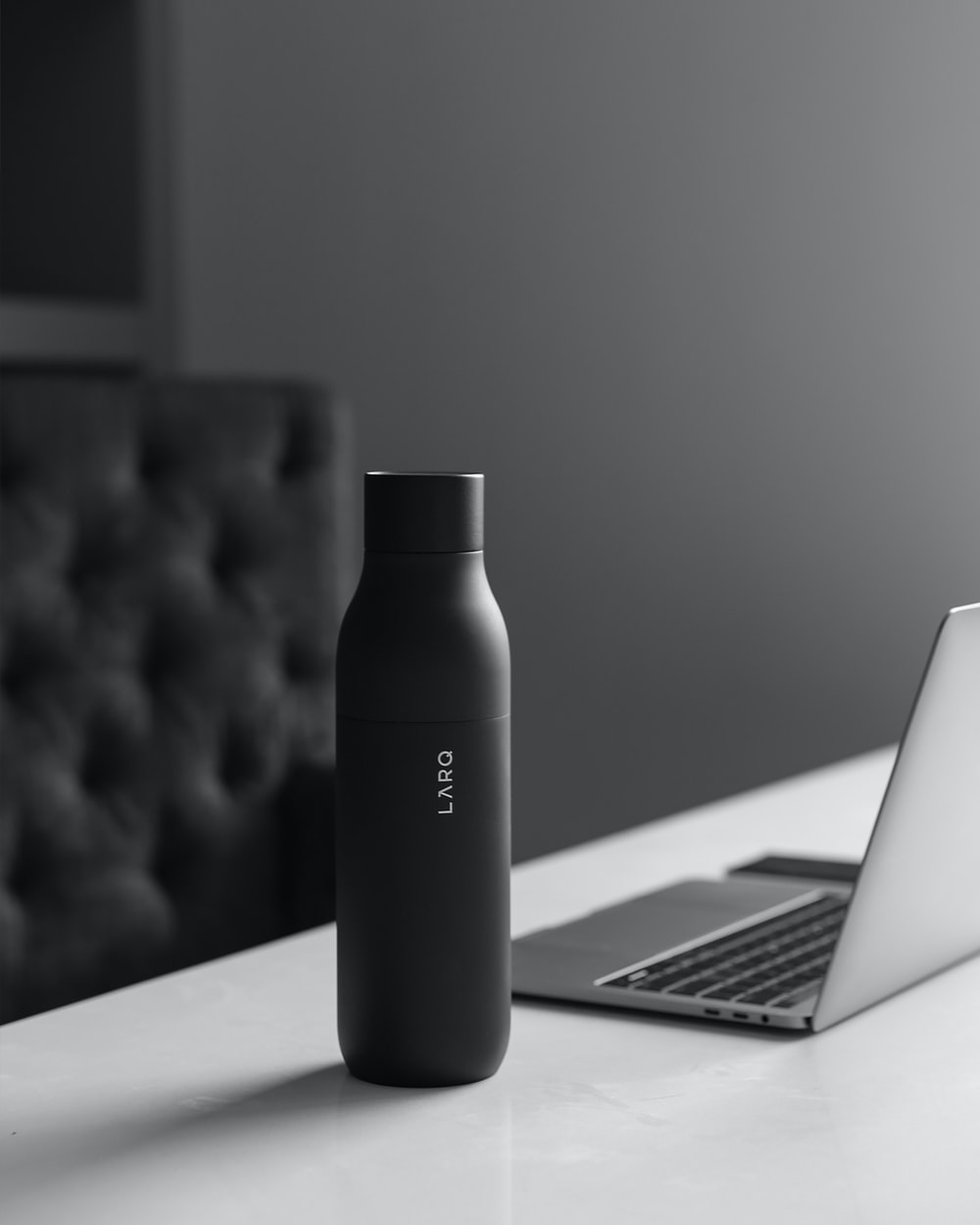 black bottle beside silver laptop computer on table