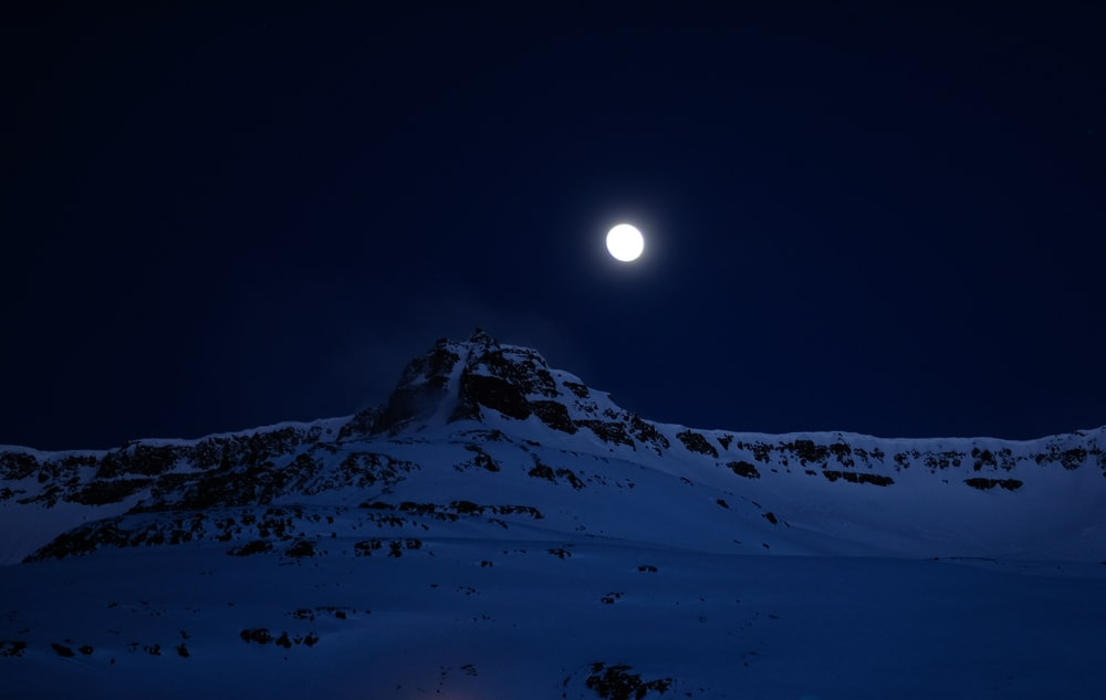 mountain covered with snow during night time
