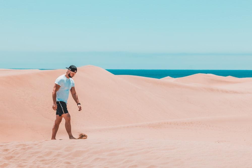 man wearing teal crew-neck shirt and black short walking on sand dune