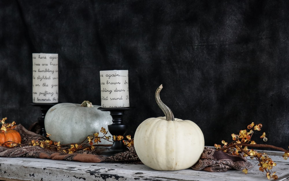 white pumpkin near two white pillar candles