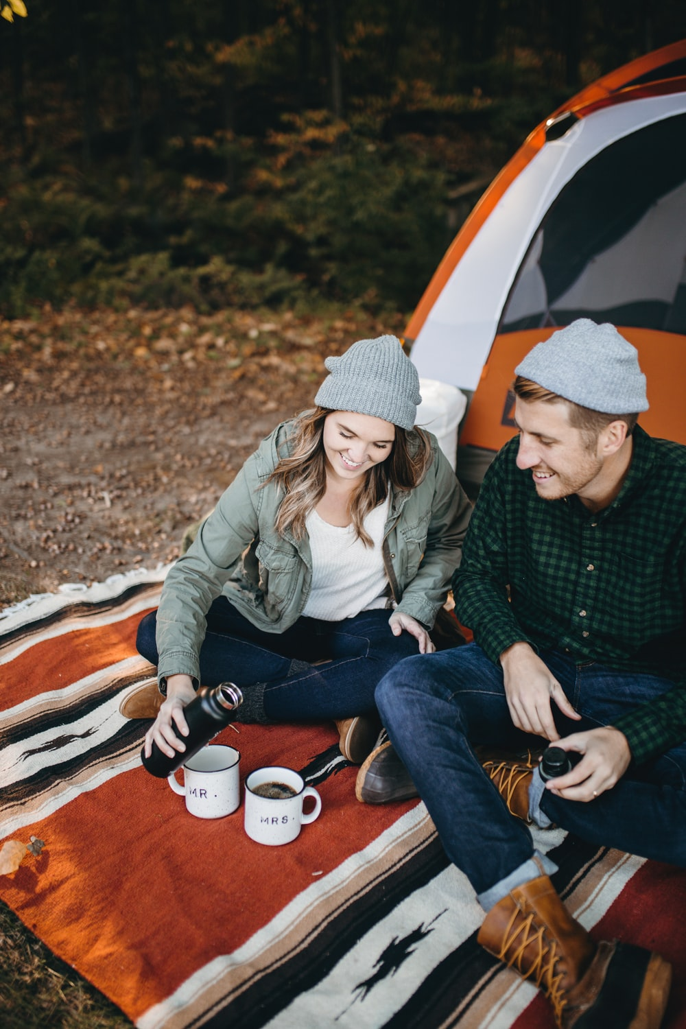 smiling man and woman sitting outside tent with two mugs
