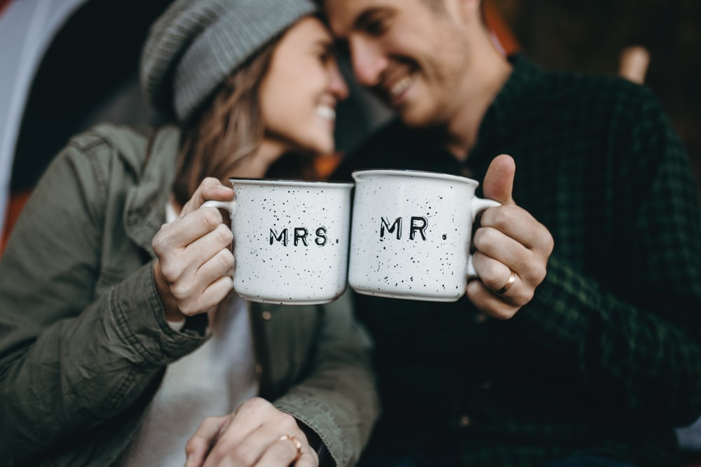 smiling man and woman holding Mrs. and Mr. mugs