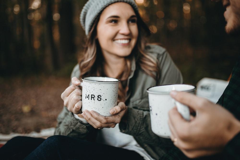 woman holding white mugs