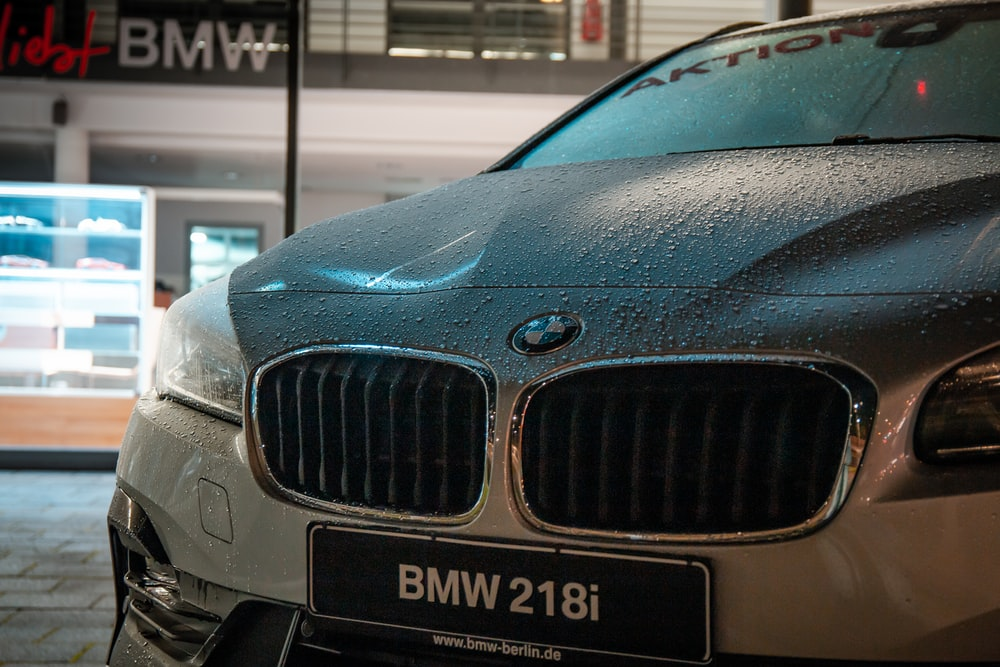 wet gray BMW car parked near building