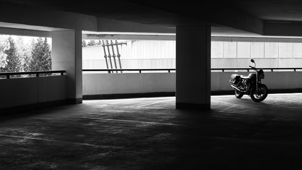 grayscale photo of motorcycle parked inside building