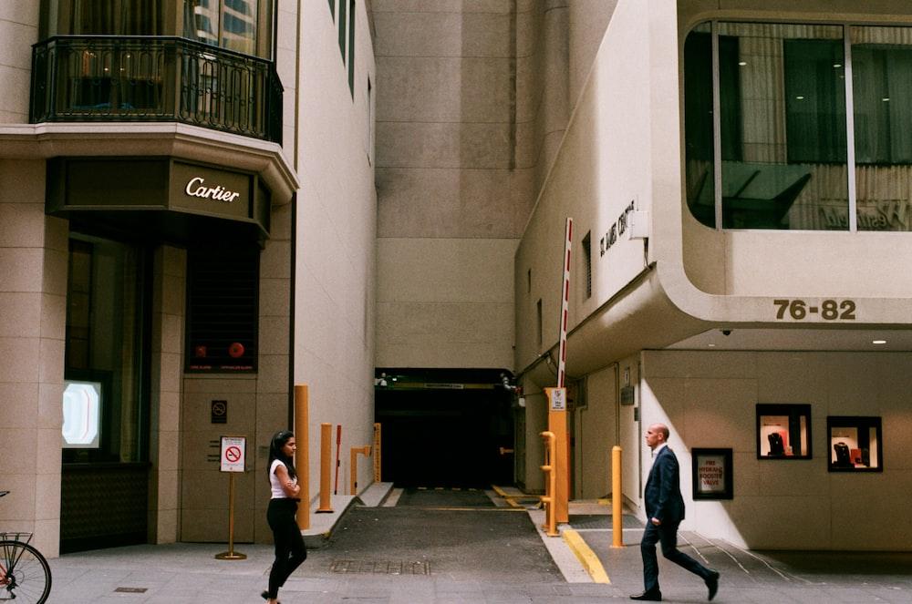 people walking beside concrete buildings during daytime