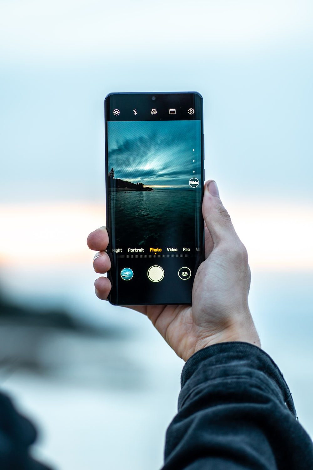 person using smartphone taking photo of body of water