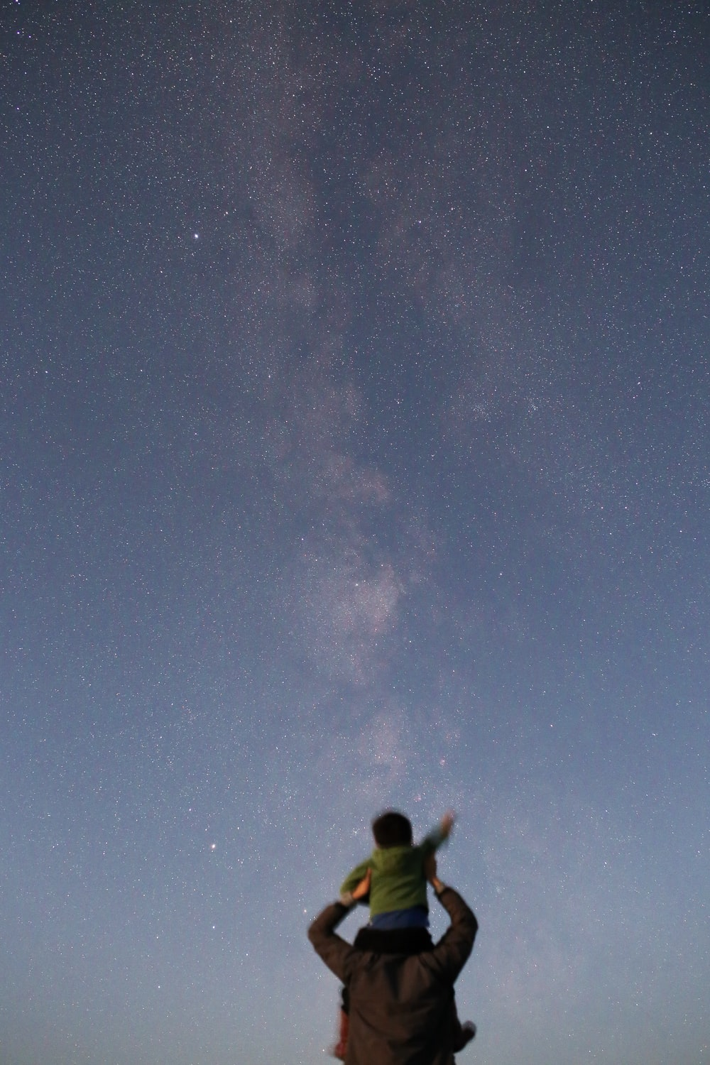 toddler on man's elbow under starry sky
