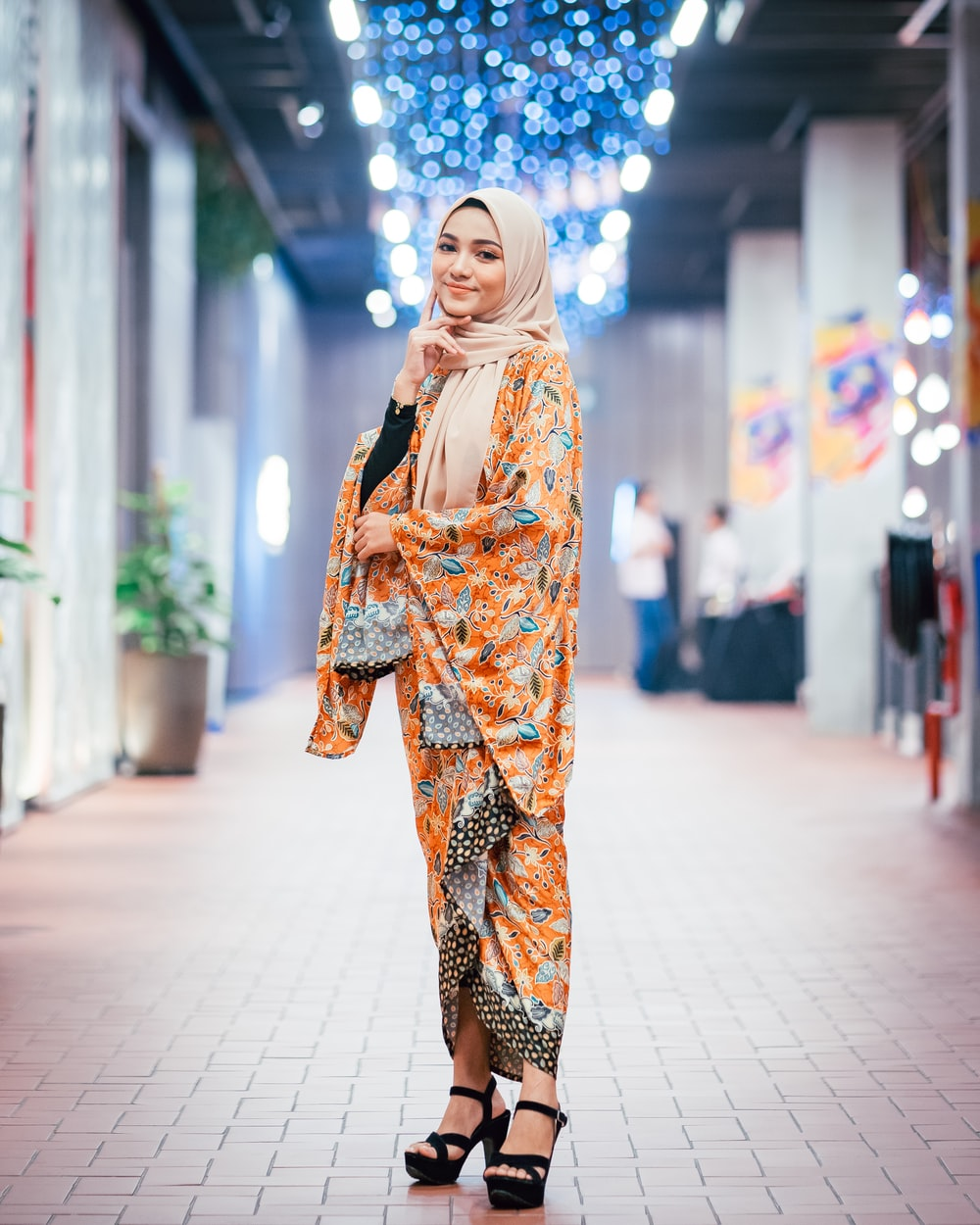 woman wearing orange and multicolored abaya dress standing and smiling