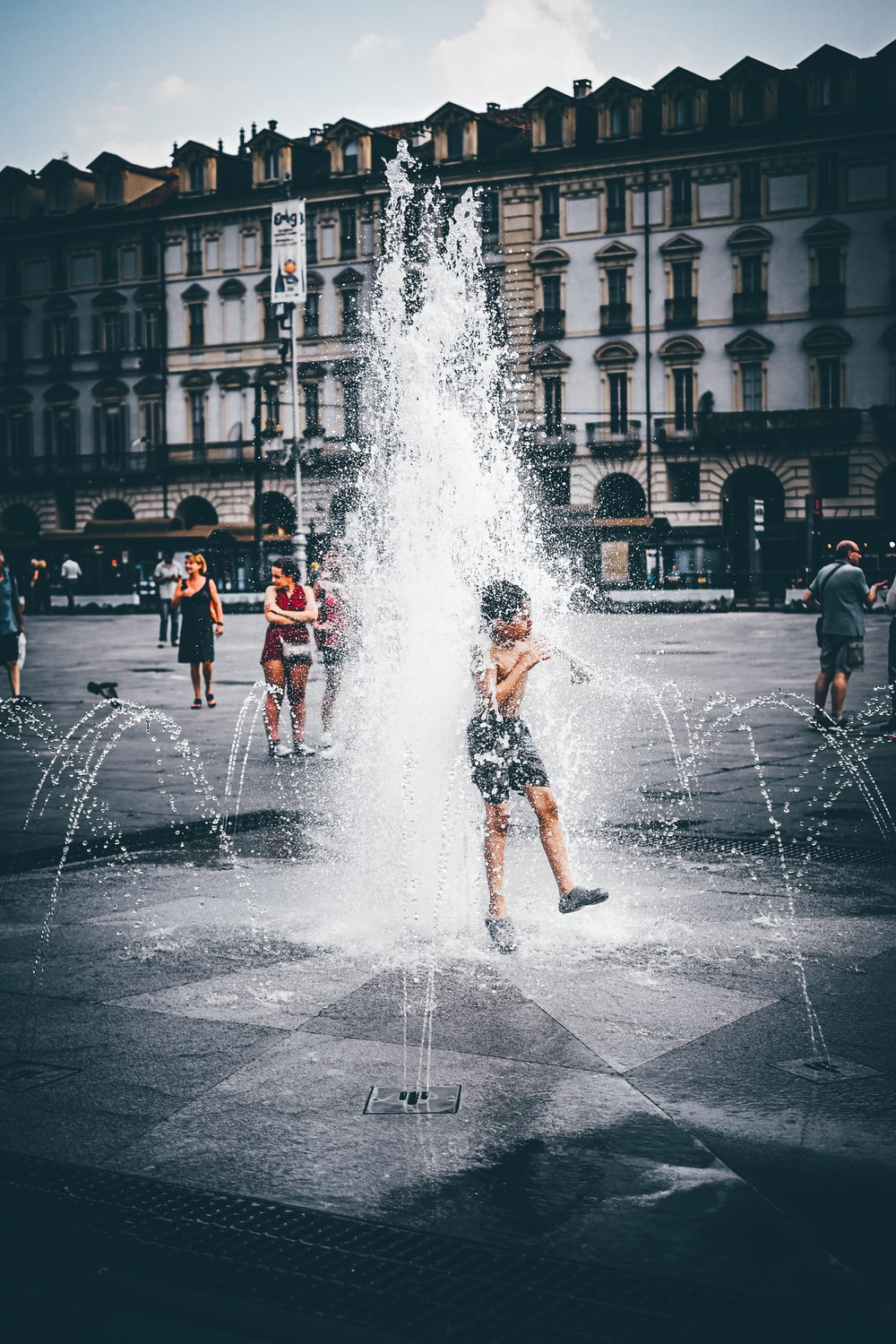topless boy wearing black shorts playing on outdoor water fountain near people walking beside buildings during daytime