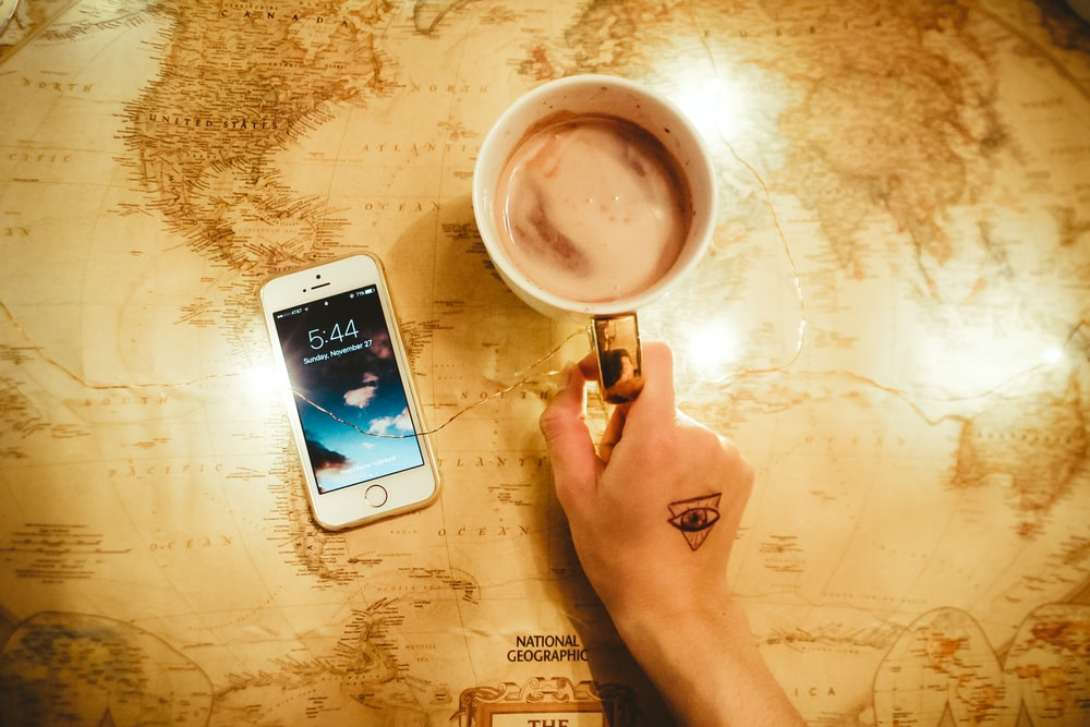 person holding mug beside iPhone 5s
