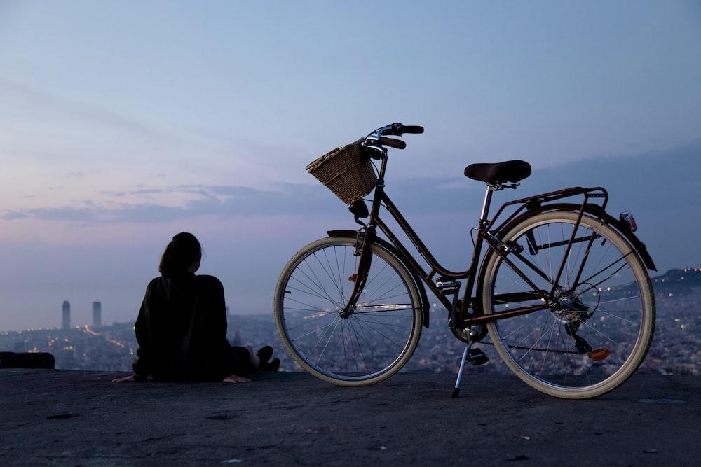 person sitting beside black and white rigid bike