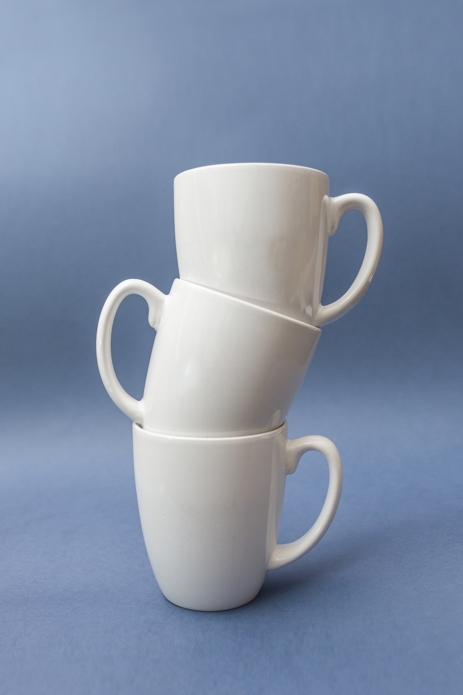 three stacked white ceramic cups