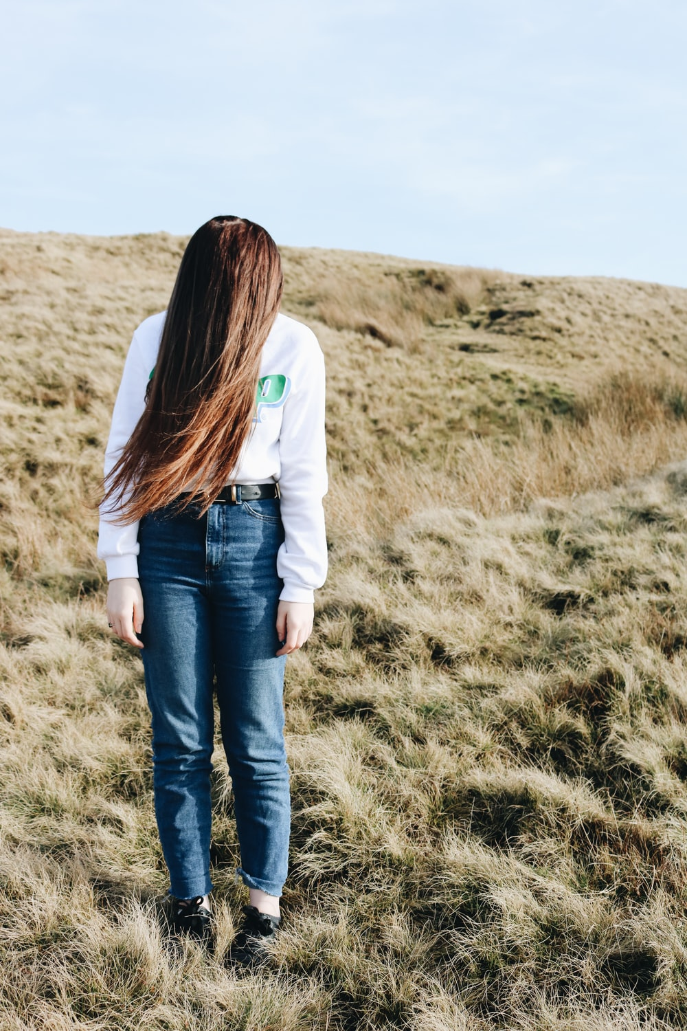 woman wears white jacket and blue denim jeans