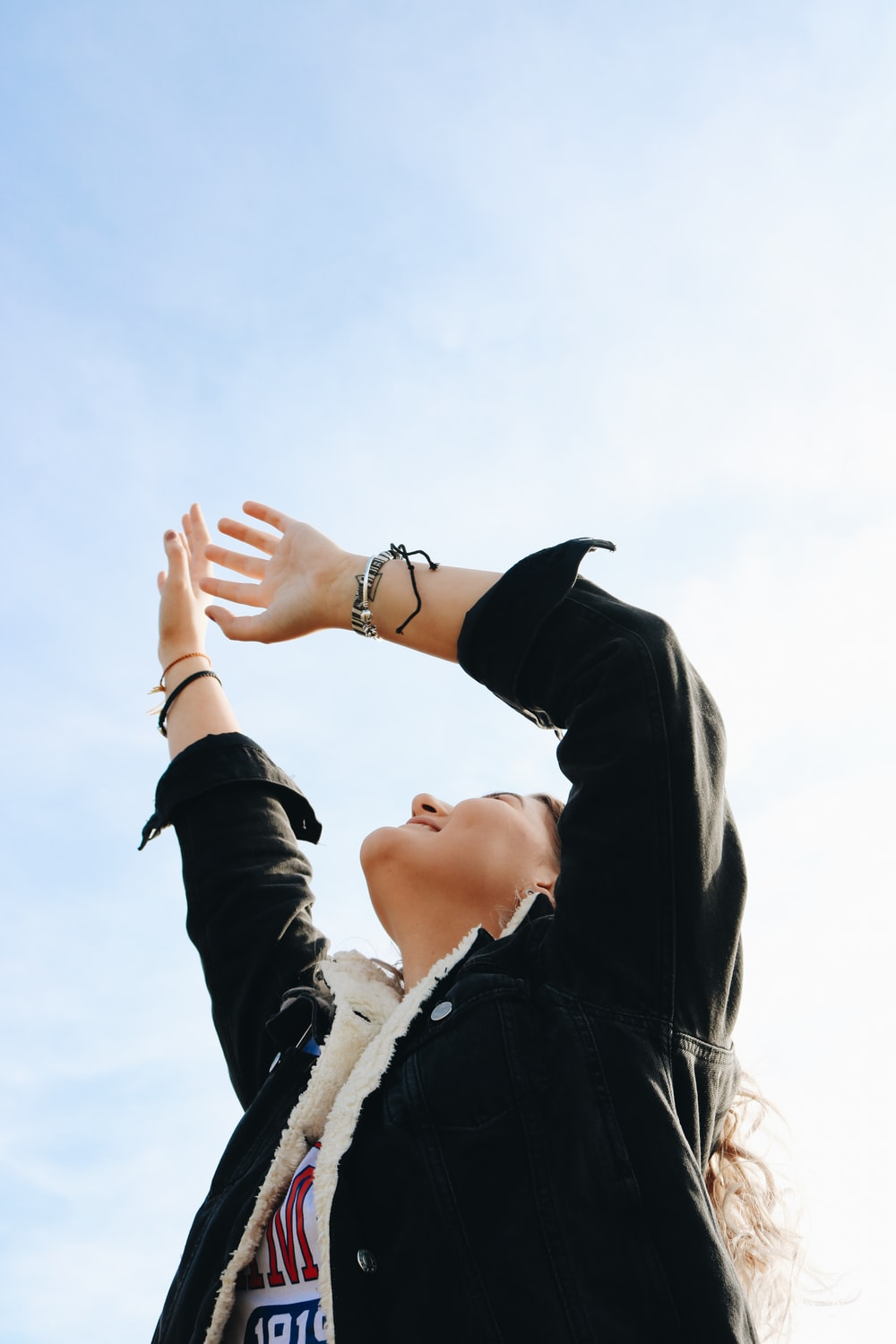 smiling woman wearing black and white jacket raising both hands while looking up under white and blue sky during daytime