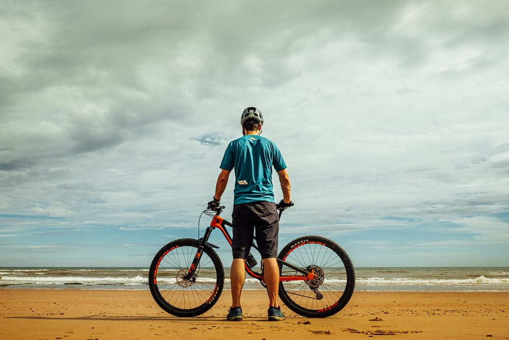 man standing beside bike on seashore