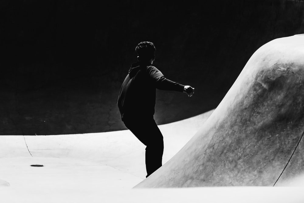 grayscale photo of man skating