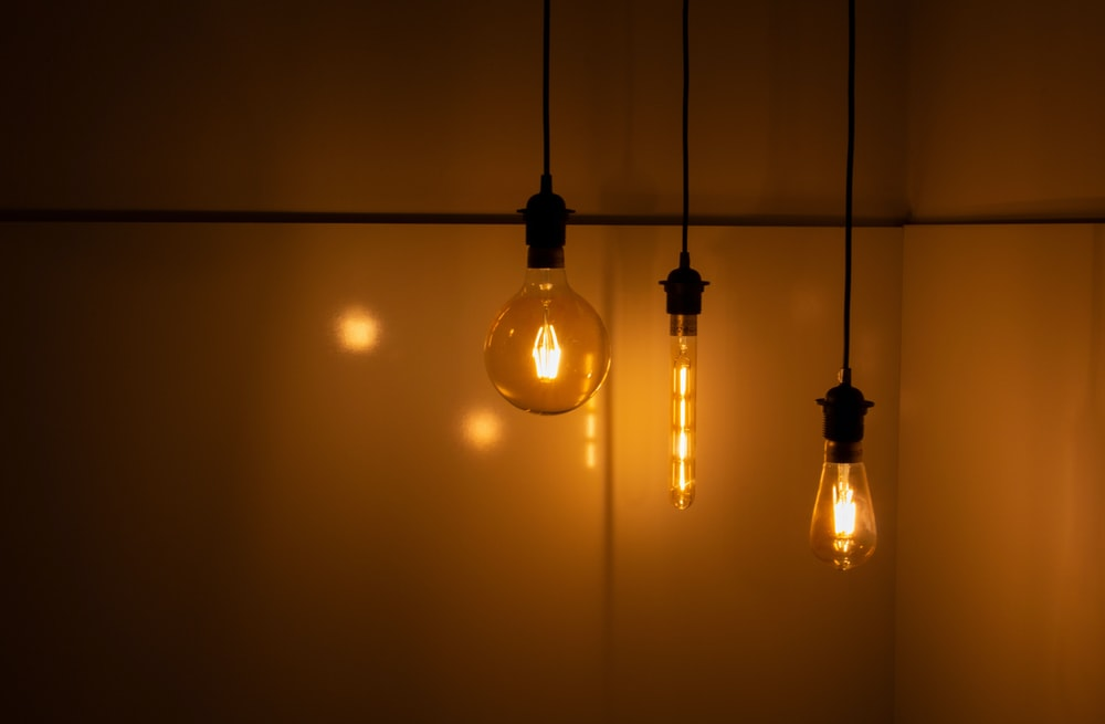 three clear light bulbs near wall