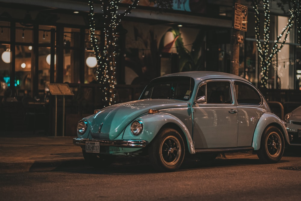 classic silver Volkswagen Beetle coupe parked beside curb