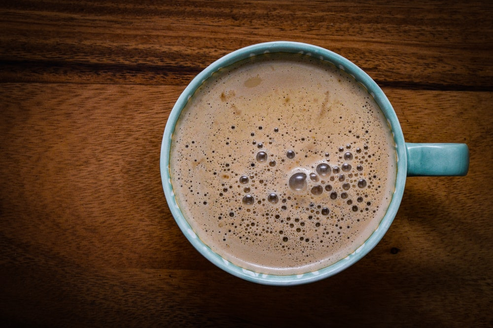 coffee inside cup on brown wooden surface