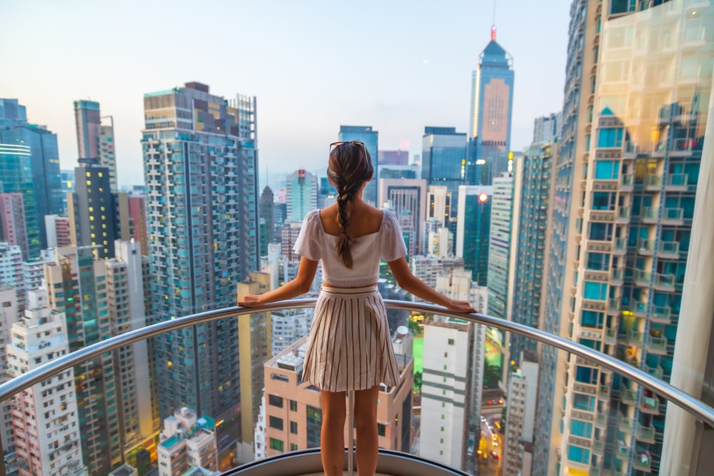 woman standing near gray stainless steel railings viewing city with high-rise buildings during daytime
