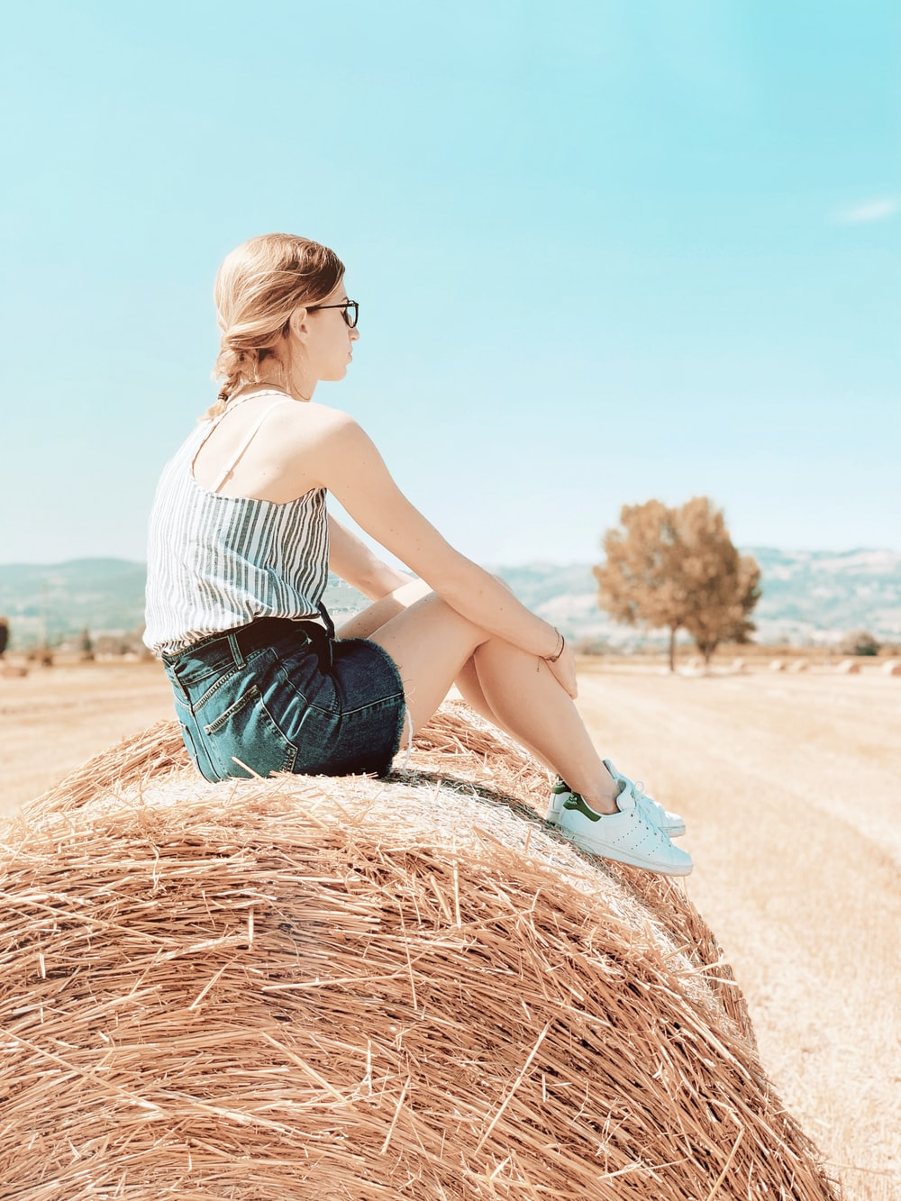 woman in white top sitting on hay