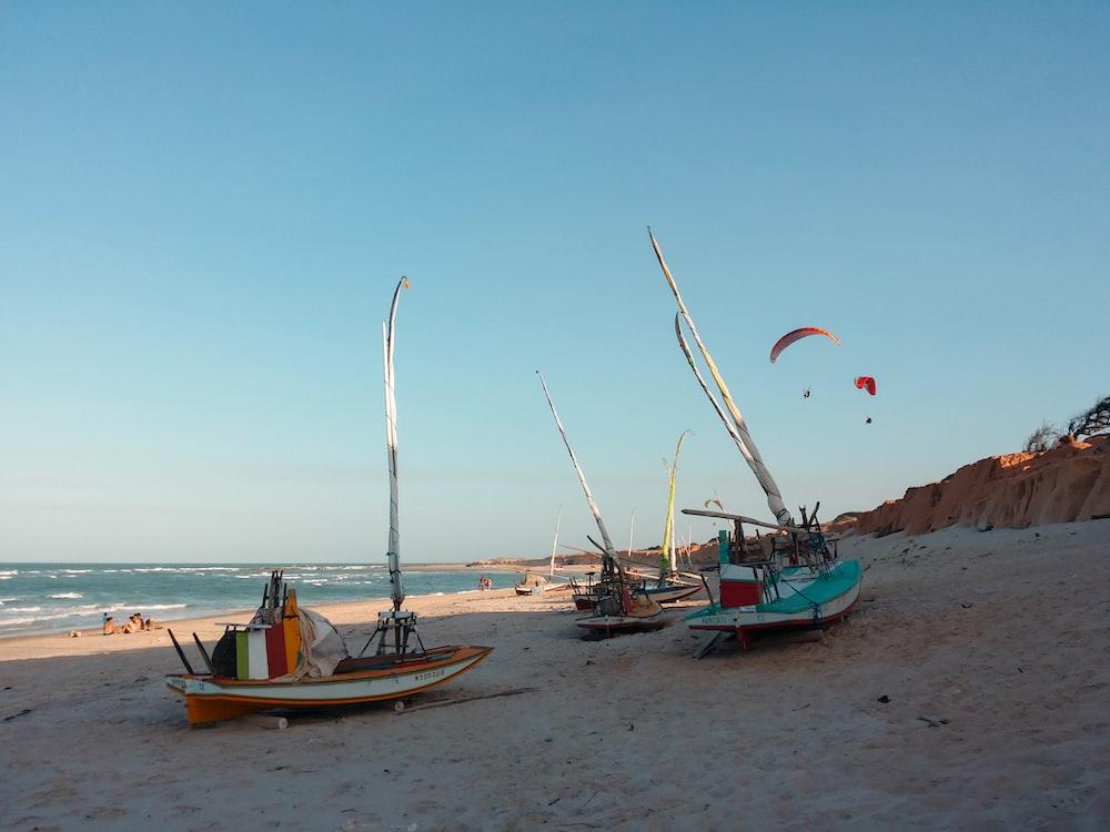 three white boats on seashore during daytime