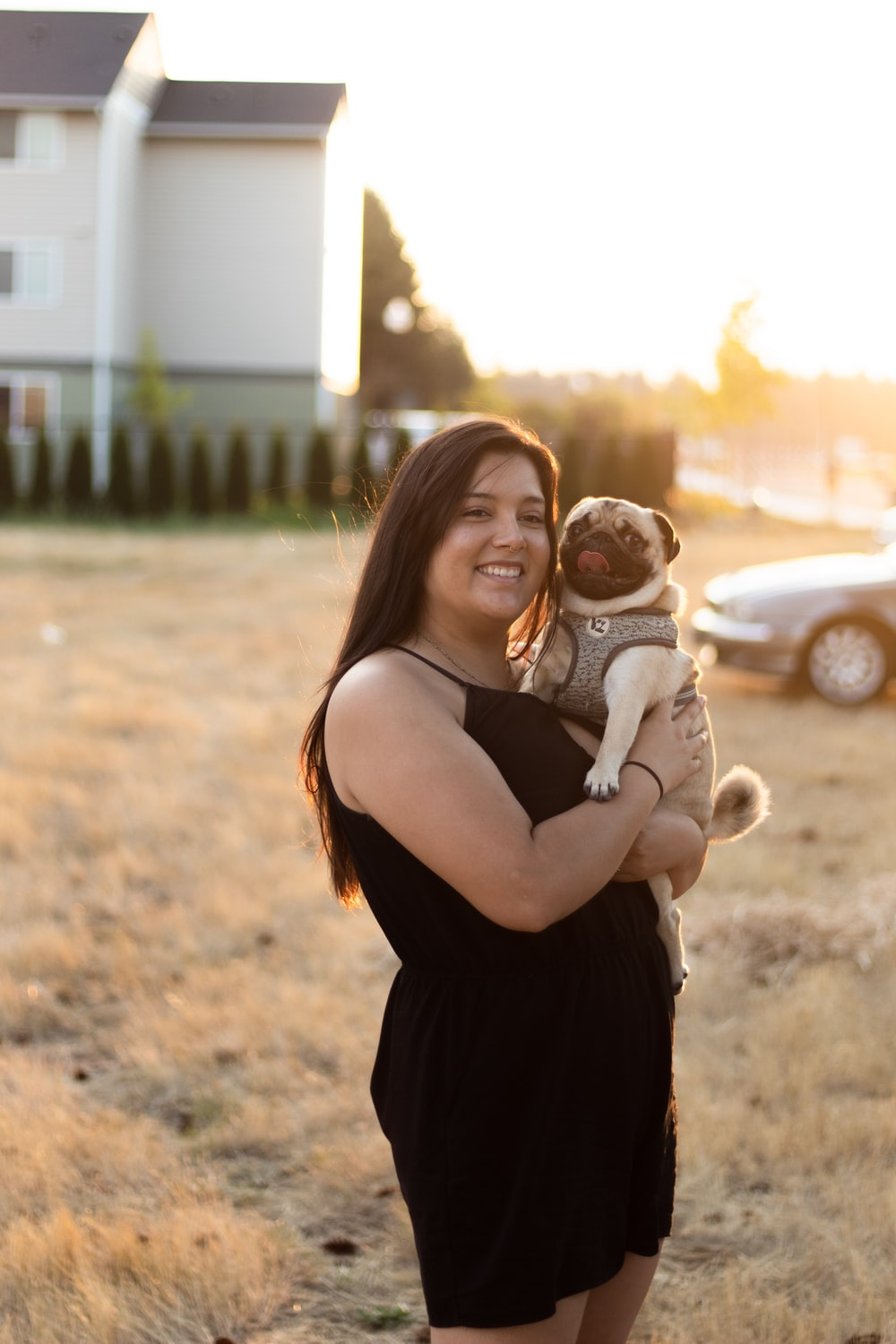 smiling woman holding pug during daytime
