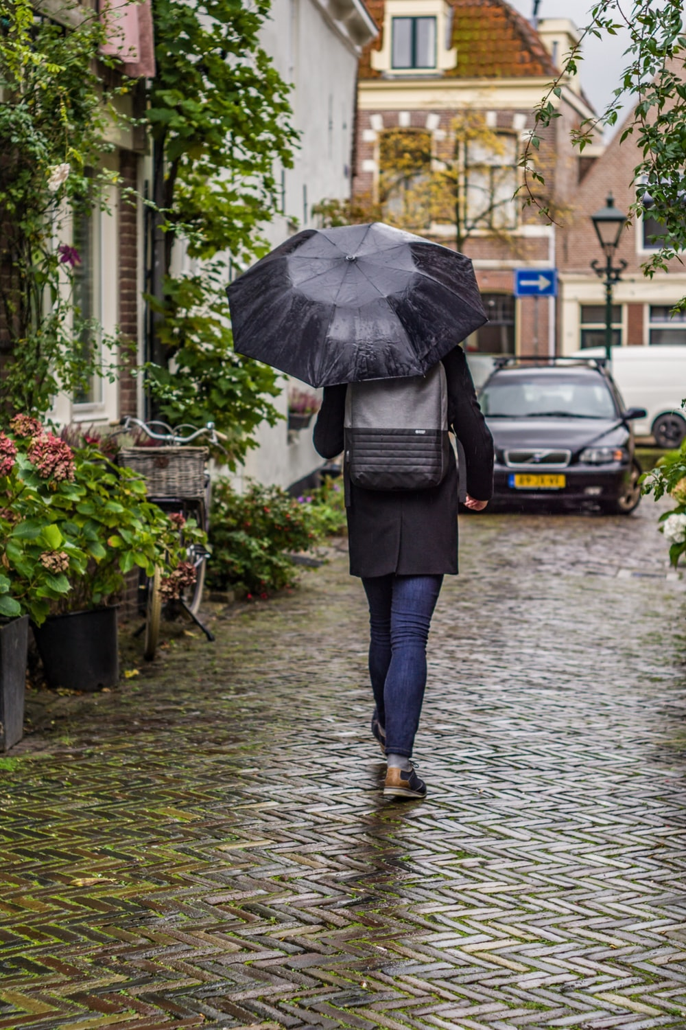person walking on road while holding umbrella
