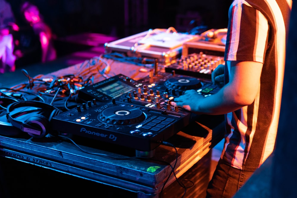 person standing while using DJ mixer