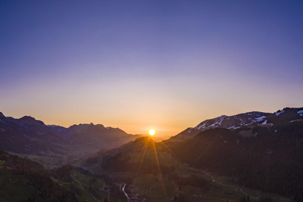 sun rays coming through mountain during daytime