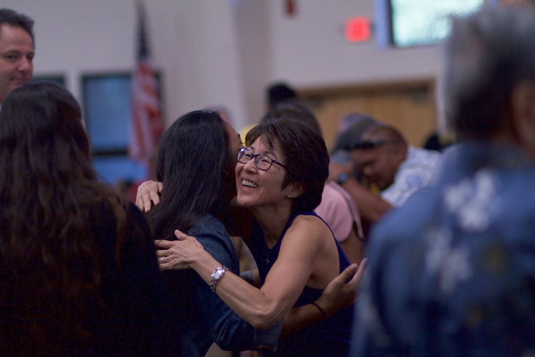 People hugging at church, woman in focus