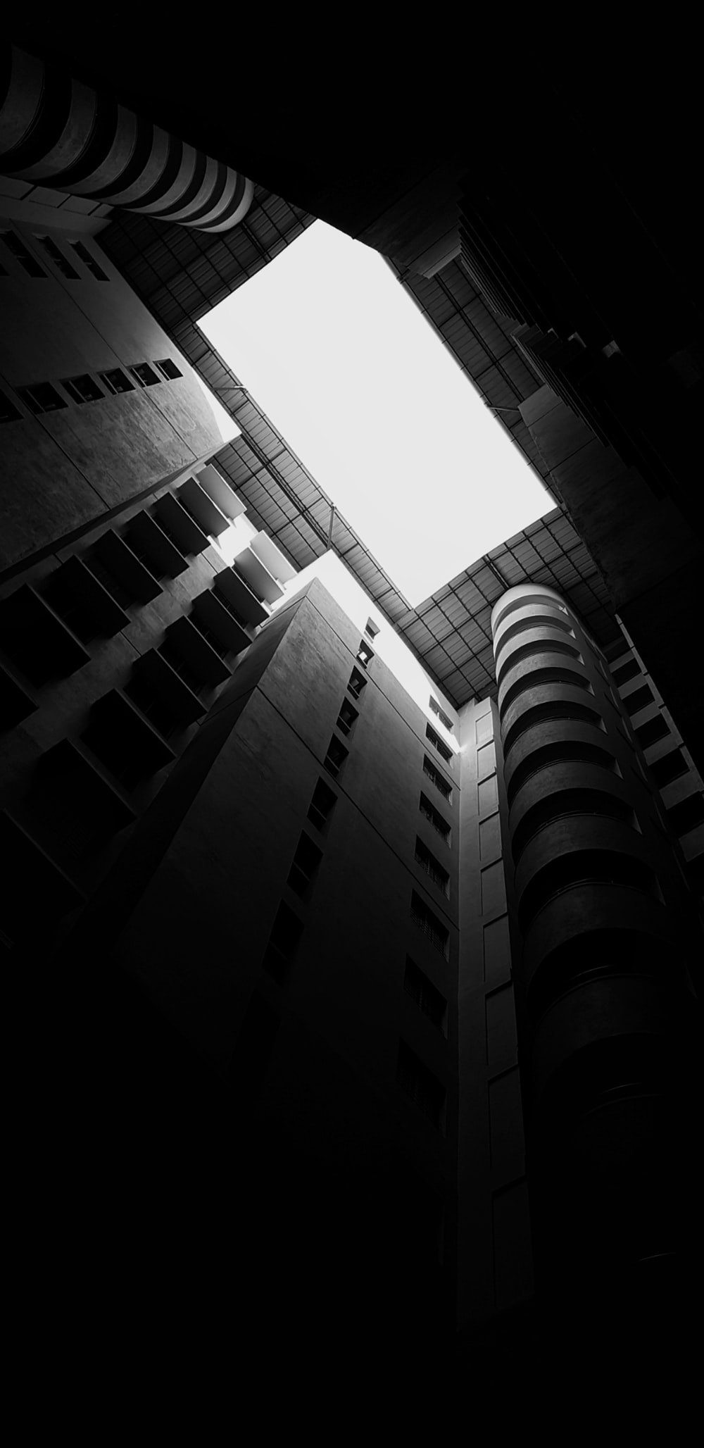 low-angle grayscale photography of a high-rise building