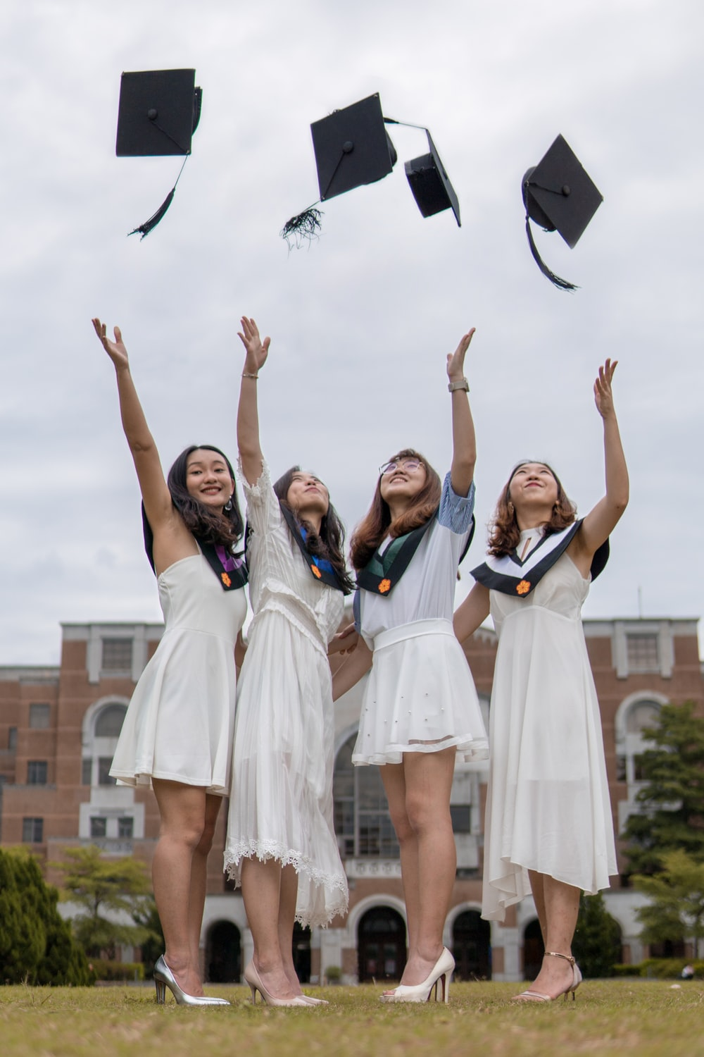 low-angle photography of four girls throwing mortar hat near outdoor during daytime