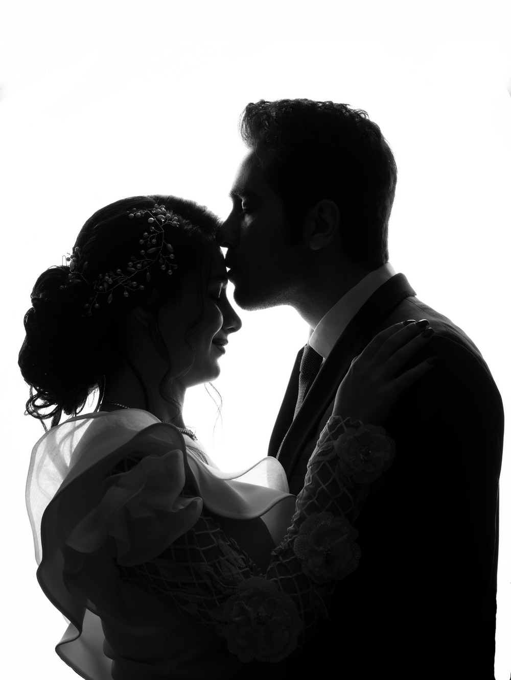 silhouette of man kissing forehead of woman